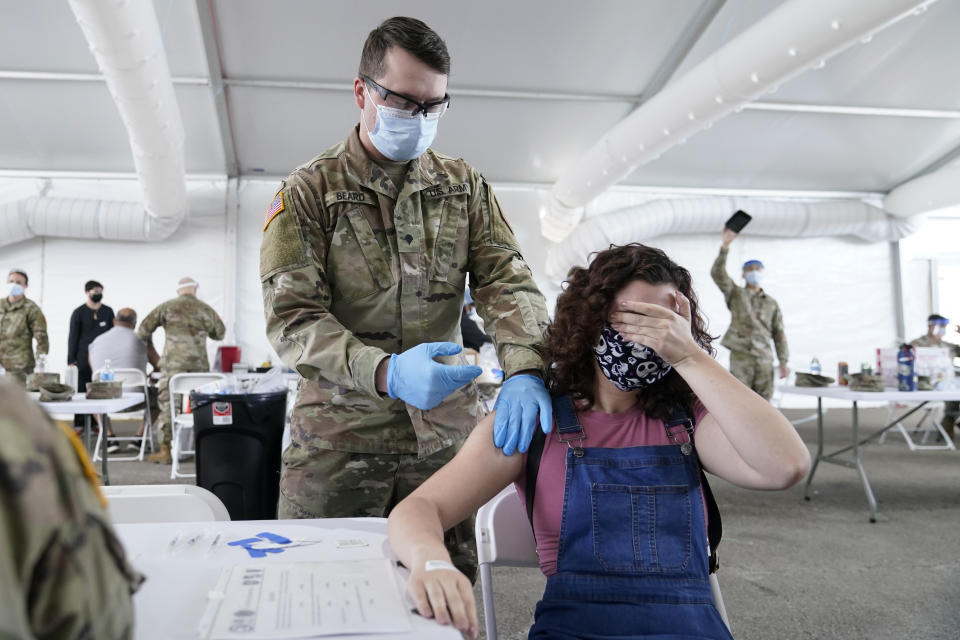 Leanne Montenegro, 21, covers her eyes as she doesn't like the sight of needles, while she receives the Pfizer COVID-19 vaccine at a FEMA vaccination center at Miami Dade College in Miami on April 5, 2021. (Lynne Sladky/AP)