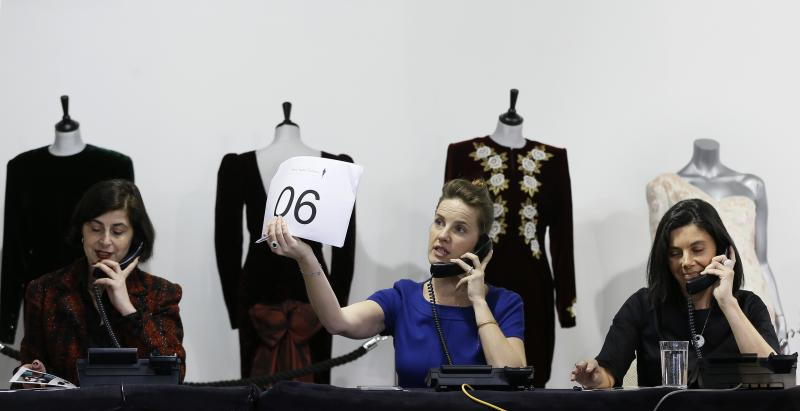 Auction house workers take telephone bids during the Kerry Taylor 'Fit for a Princess' auction in London, Tuesday, March 19, 2013. The auction was of ten dresses formerly owned and worn by Britain's Princess Diana. The total hammer price for the ten lots was 719,000 pounds ($1.09 million US) not including the 20 percent buyers premium . (AP Photo/Kirsty Wigglesworth)