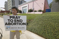 FILE - In this Oct. 2, 2019. file photo, an abortion opponent sings to herself outside the Jackson Womens Health Organization clinic in Jackson, Miss. The Supreme Court has agreed to hear a potentially ground-breaking abortion case, and the news is energizing activists on both sides of the contentious issue. They're already girding to make abortion access a high-profile issue in next year's midterm elections. (AP Photo/Rogelio V. Solis, File)