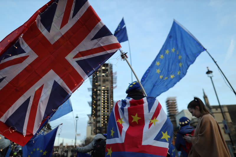 A man is seen holding EU and Britain flag outside the Houses of Parliament in London