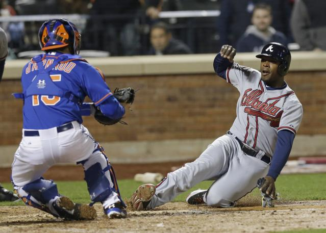 New York Mets catcher Travis d'Arnaud (15) tags out Atlanta Braves' Justin Upton during the eighth inning of a baseball game on Friday, April 18, 2014, in New York. (AP Photo/Frank Franklin II)