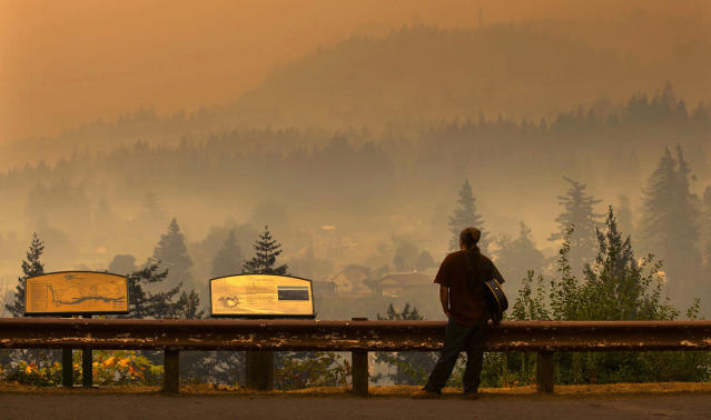 <p>Jason Wheeler looks out across the Columbia River from the north side of Bridge of the Gods at the smoky community of Cascade Locks, Ore. Sept. 5, 2017 after being evacuated from his home yesterday. (Photo: Chris Pietsch/The Register-Guard via AP) </p>
