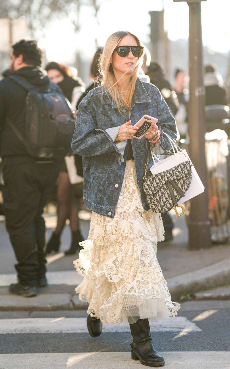 A stylish Paris Fashion Week show-goer paired her tiered lace dress with an oversized denim jacket - perfect bank holiday dressing - 2019 Edward Berthelot