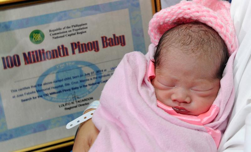 "Newly-born baby girl Jennalyn Sentino, the Philippines' ""100,000,000th baby"", sleeps in her mother's arms during a presentation at a government hospital in Manila on July 27, 2014"