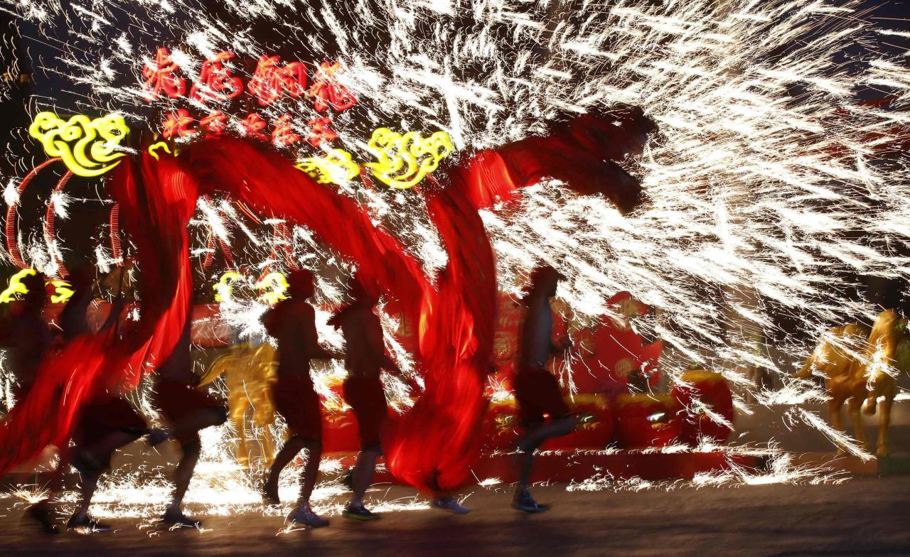 Dancers perform a fire dragon dance in the shower of molten iron spewing firework-like sparks during a folk art performance to celebrate the traditional Chinese Spring Festival on the first day of the Chinese Lunar New Year, which welcomes the Year of the Horse, at the Happy Valley amusement park in Beijing January 31, 2014. REUTERS/Kim Kyung-Hoon (CHINA - Tags: ANNIVERSARY SOCIETY TPX IMAGES OF THE DAY)