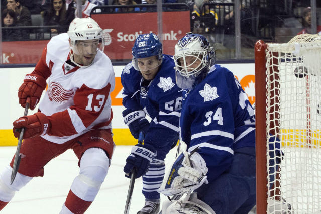Detroit Red Wings' Luke Glendening, left, battles for the puck with Toronto Maple Leafs' Morgan Rielly during first period NHL hockey action in Toronto on Saturday, December 21, 2013. THE CANADIAN PRESS/Chris Young