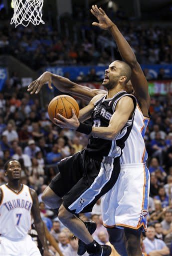 San Antonio Spurs guard Tony Parker, center, of France, is fouled by Oklahoma City Thunder forward Serge Ibaka, right, of Republic of Congo, as he shoots in the second quarter of an NBA basketball game in Oklahoma City, Friday, March 16, 2012. Thunder guard Royal Ivey is at left. (AP Photo/Sue Ogrocki)