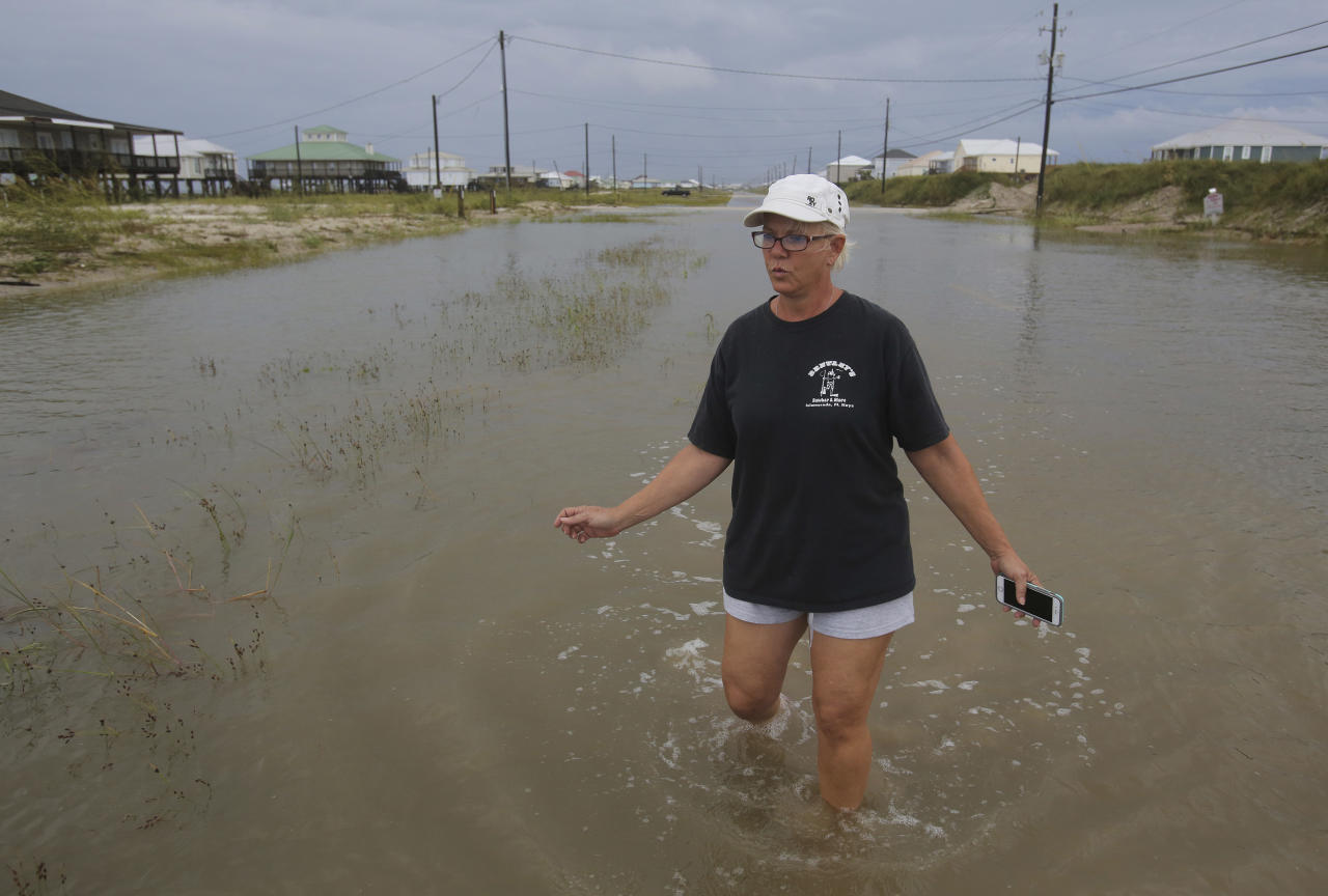<p>Susan Jones walks through a flooded road from Tropical Storm Gordon, Wednesday, Sept. 5, 2018, in Dauphin Island, Ala. (Photo: Dan Anderson/AP) </p>