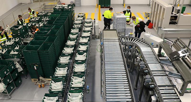 Employees sort through baskets of online orders that come off a conveyor belt. Source: Woolworths