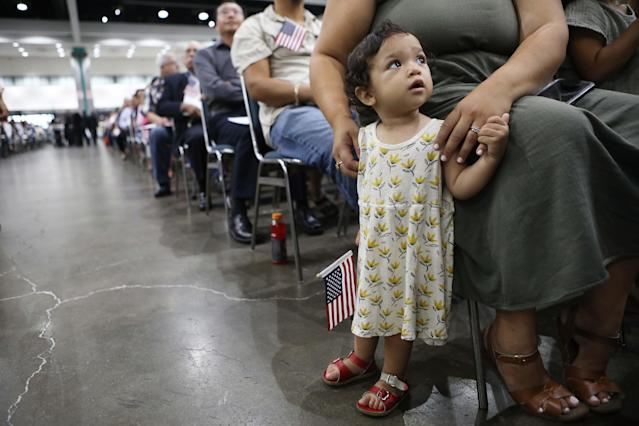Esme Gomez, already a citizen, waits before her father, from El Salvador, is sworn in as a U.S. citizen in Los Angeles. (Photo: Joe Raedle/Getty Images)