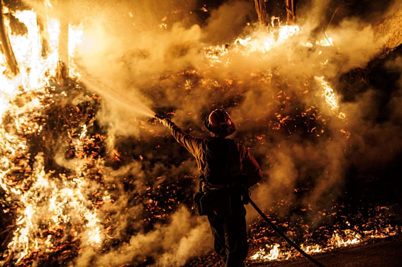 A firefighter sprays water while battling the spread of the Maria Fire as it moved quickly towards Santa Paula, California, on Nov. 1, 2019.  (Photo: Marcus Yam/Los Angeles Times via Getty Images)