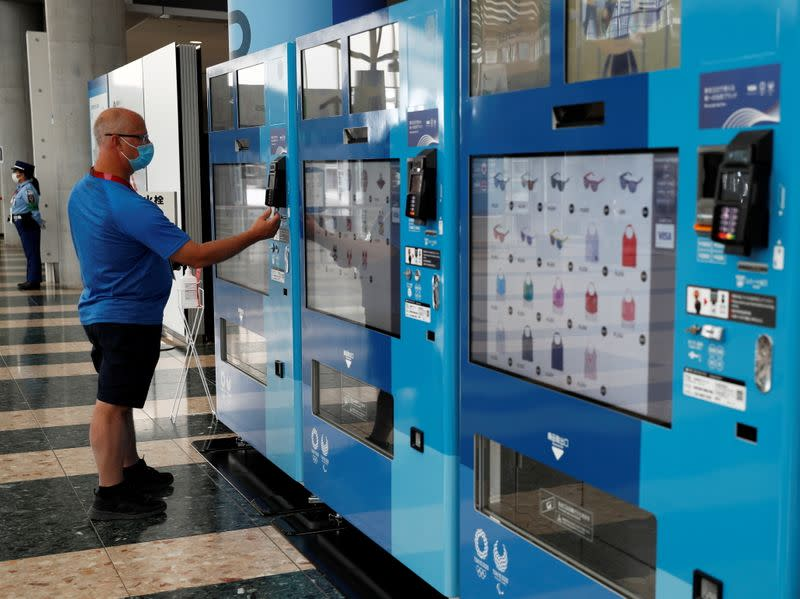 Technician John Einarson of Canada purchases a Tokyo 2020 souvenir from a vending machine at the Olympic Main Press Center in Tokyo