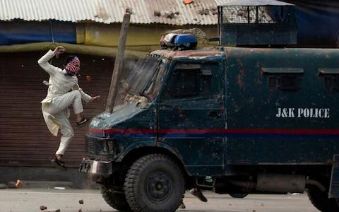 A masked Kashmiri protester jumps on the bonnet of an armored vehicle of Indian police as he throw stones at it during a protest in Srinagar, Indian controlled Kashmir, Friday, May 31, 2019. - Credit: AP