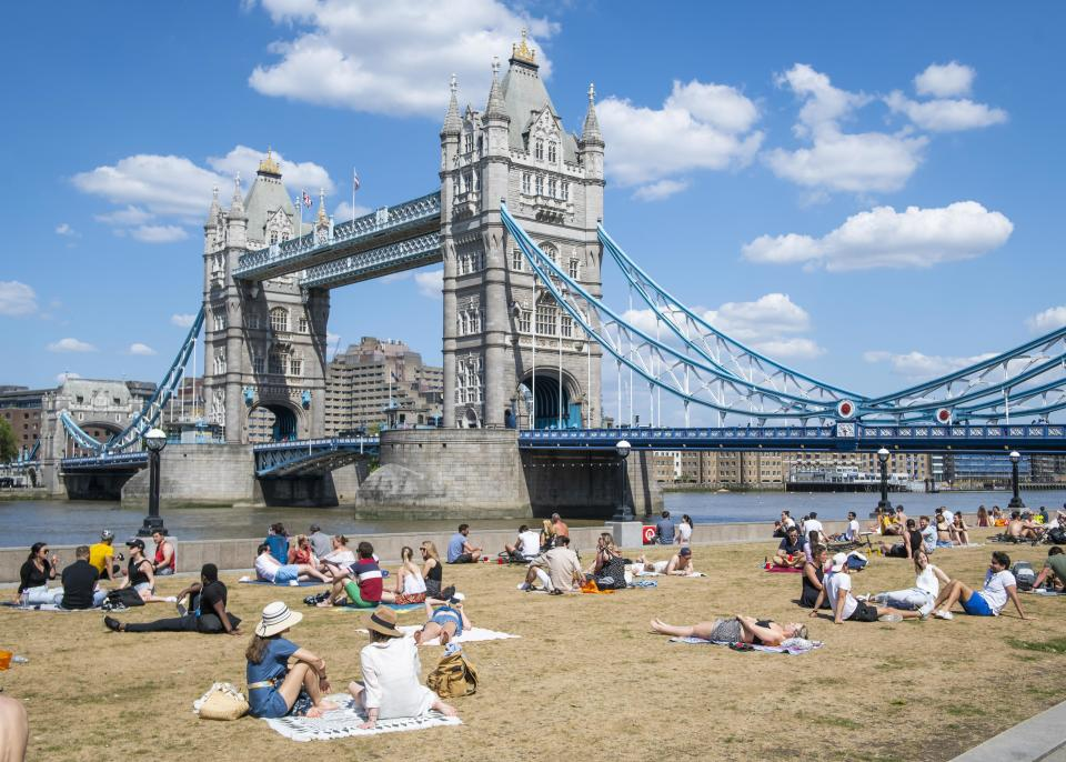 People enjoy the Bank Holiday Monday warm weather in front of Tower Bridge, in Potters Field Park,  London, as people head outside with lockdown measures eased. Picture date: Monday 25th May 2020. Photo credit should read: David Jensen/EMPICS Entertainment