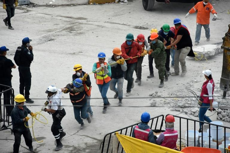 Volunteers remove rubble from a quake-flattened building in Mexico City