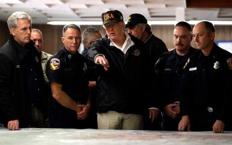 Donald Trump is briefed by emergency workers during his visit - Credit: Evan Vucci/AP