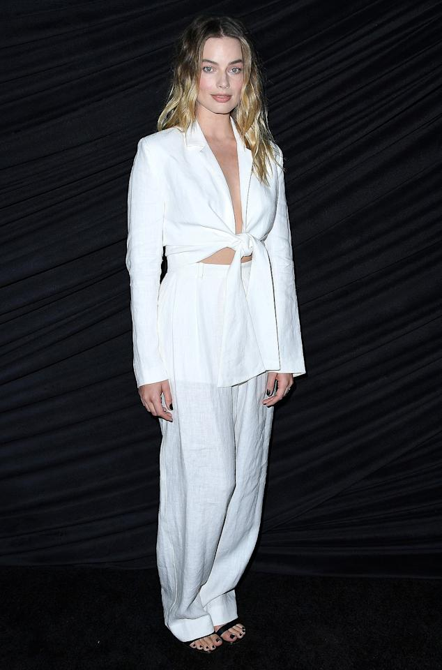 in a Mara Hoffman white linen front-tie long-sleeve crop top and matching trousers, paired with black heeled sandals at the special screening <em>Bombshell</em> in West Hollywood.