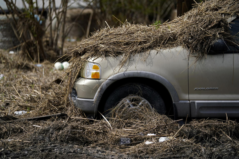 Marsh grass, displaced from floodwaters, sits on a car in Ironton, La., Monday, Sept. 27, 2021. A month after Hurricane Ida, small communities along Louisiana's southeastern coast are still without power or running water. Some residents have lost most of their possessions to the storm's floodwaters. (AP Photo/Gerald Herbert)