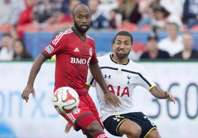Toronto FC's Collen Warner, left, and Tottenham Hotspur's Aaron Lennon battle for the ball during the first half of a friendly soccer match in Toronto on Wednesday, July 23, 2014. (AP Photo/The Canadian Press, Darren Calabrese)
