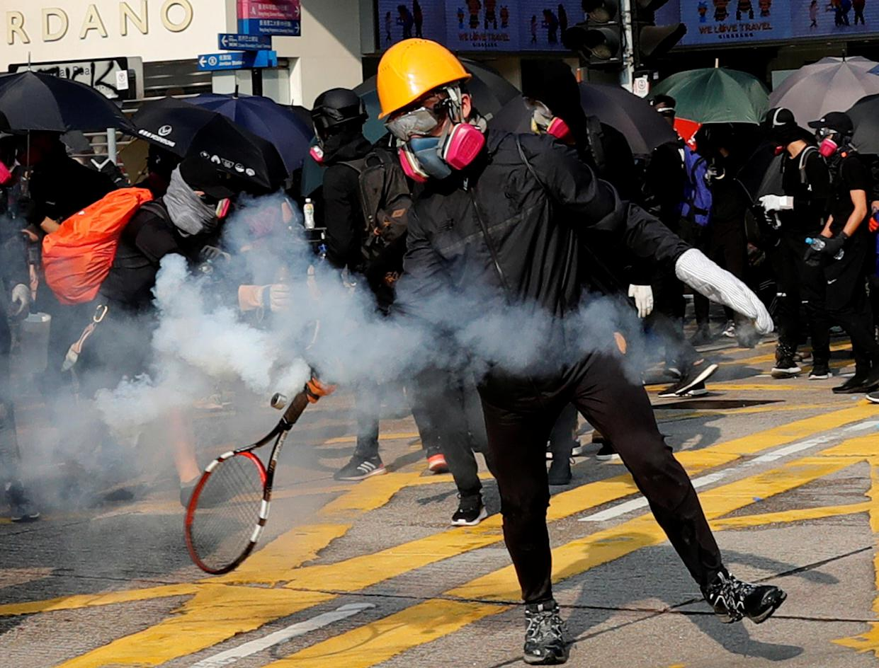 An antigovernment demonstrator lobs back a tear gas canister with a tennis racket in Hong Kong, Oct. 20, 2019. (Photo: Kim Kyung-Hoon/Reuters)