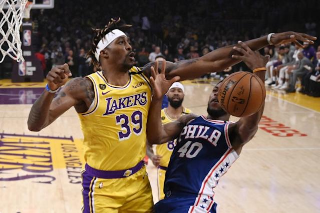 """Lakers center Dwight Howard, seen here blocking a shot by 76ers forward Glen Robinson III, has decided he will take part in the NBA season restart in Orlando. <span class=""""copyright"""">(Mark J. Terrill / Associated Press)</span>"""