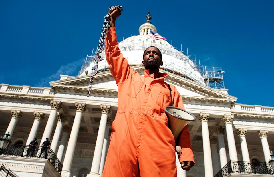 An activist dressed as a prisoner stands in front of the US Capitol Building during a rally for Congress of Conscience on Capitol Hill April 18, 2016 in Washington, DC. (Photo: BRENDAN SMIALOWSKI/AFP via Getty Images)