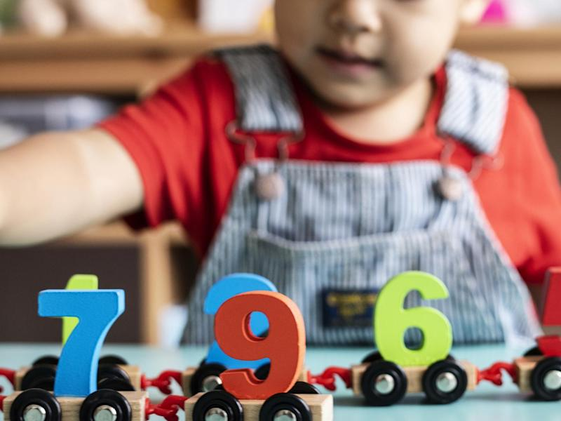 Little boy playing mathematics wooden toy at nursery: Getty Images/iStockphoto