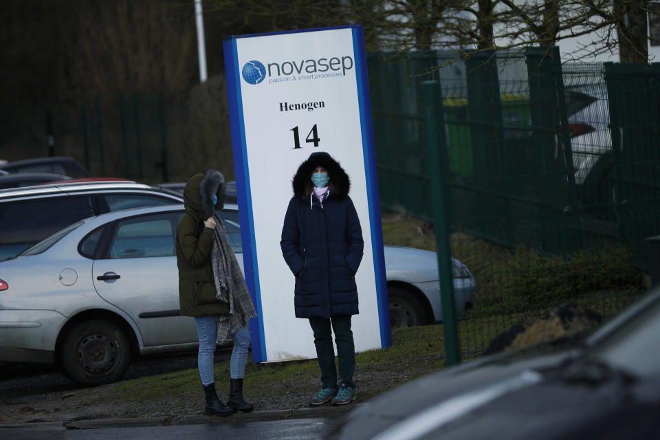 People, wearing face masks to prevent the spread of the coronavirus, stand next to the entrance of the Novasep factory in Seneffe, Belgium, Friday, Jan. 29, 2021. The European Union has made public a redacted version of the contract it agreed with the drugmaker AstraZeneca which lies at the heart of a major row over coronavirus vaccine deliveries. (AP Photo/Francisco Seco)