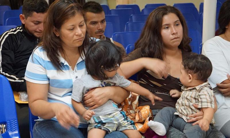 Mothers and children wait to be assisted by volunteers in a humanitarian center in the border town of McAllen, Texas, on 18 June.