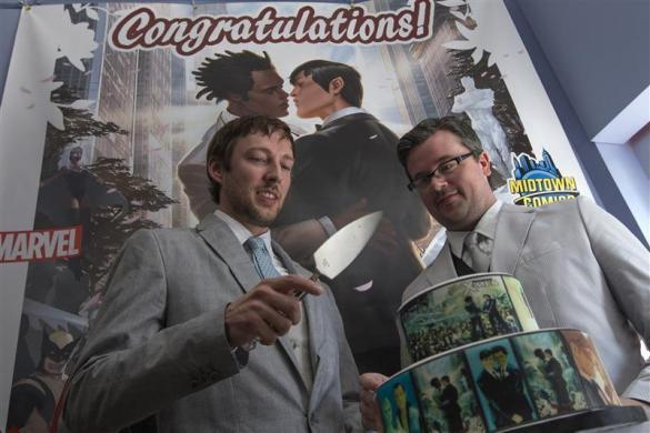Jason Welker (L) and Scott Everhart prepare to cut a cake after exchanging vows during their wedding ceremony at a comic book retail shop in Manhattan, New York June 20, 2012.