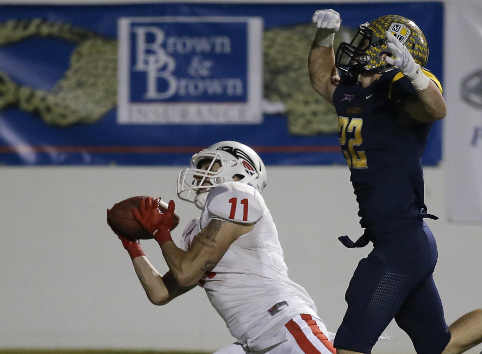 Southern Oregon wide receiver Dylan Young (11) catches a pass for a touchdown in front of Marian's Eric Price, right, during the second half of an NAIA Football National Championship game in Daytona Beach, Fla., Friday, Dec. 19, 2014. Southern Oregon won 55-31. (AP Photo/John Raoux)