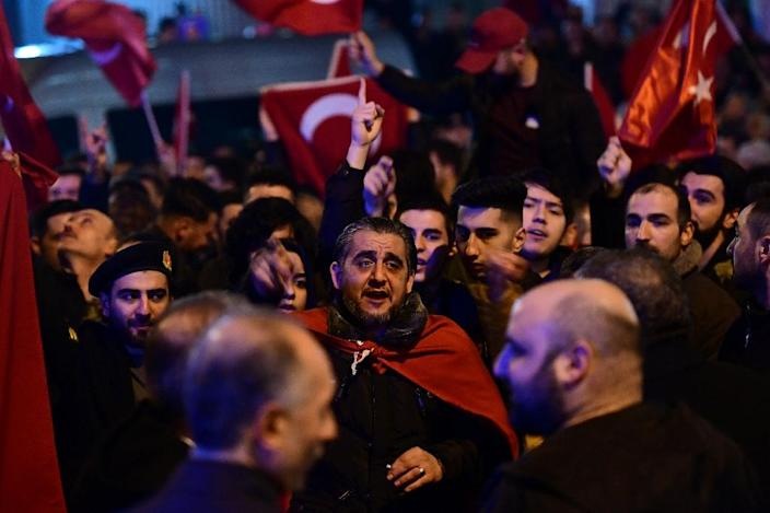 People gesture and wave flags as Turkish residents of the Netherlands gather for a protest outside Turkey's consulate in Rotterdam on March 11, 2017 (AFP Photo/Emmanuel DUNAND)