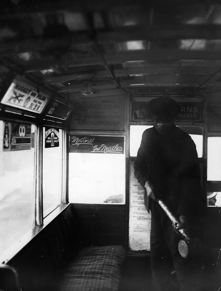 A man sprays the inside of a bus of the London General Omnibus Co with anti-flu preparation during the flu epidemic which followed the First World War, London, 2nd March 1920. (Photo by H. F. Davis/Topical Press Agency/Getty Images)