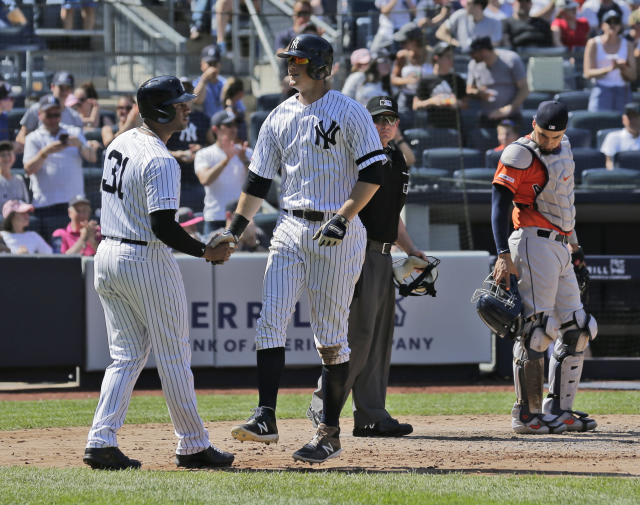 New York Yankees' DJ LeMahieu, second from left, celebrates his three-run home run with Aaron Hicks, left, while Houston Astros catcher Robinson Chirinos, right, looks on during the fifth inning of a baseball game at Yankee Stadium, Sunday, June 23, 2019, in New York. (AP Photo/Seth Wenig)
