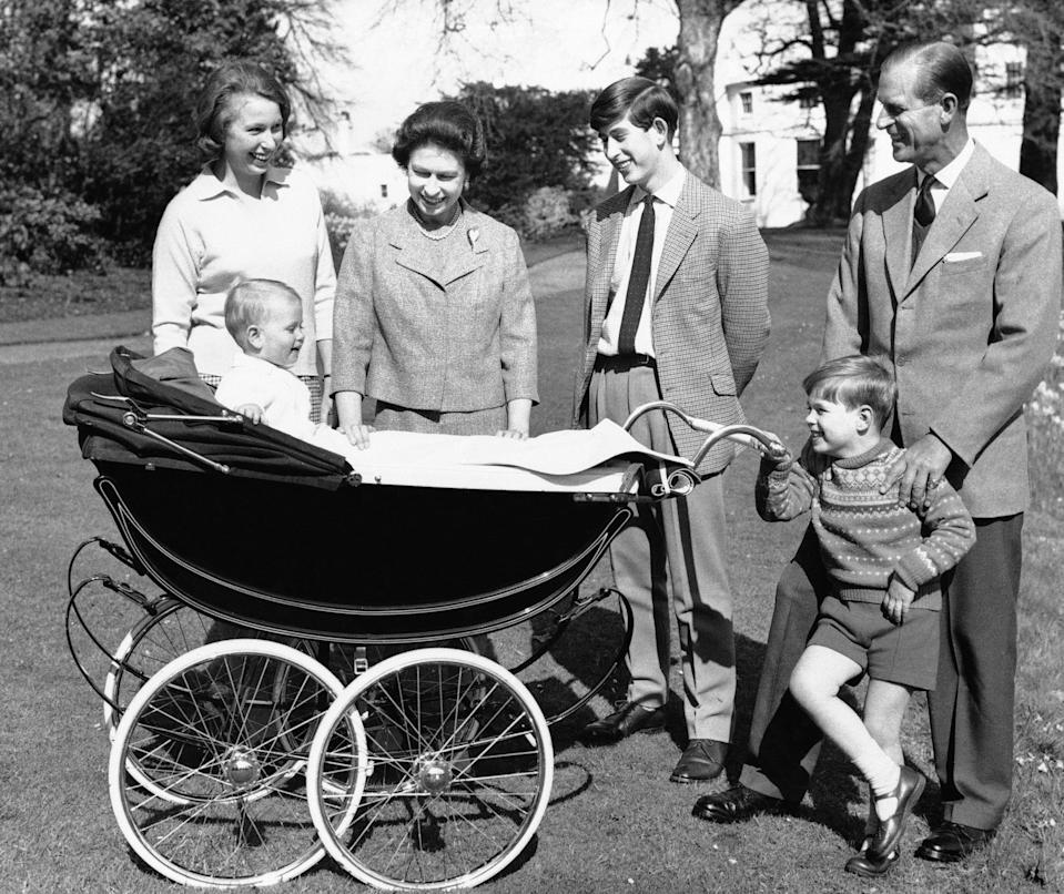In this Dec. 19, 1965 file photo, Britain's Queen Elizabeth II and Prince Philip is surrounded by member of her family on the grounds of Windsor Castle, in Windsor, England. From left, Princess Anne, Prince Charles, Prince Andrew. In the pram is Prince Edward.