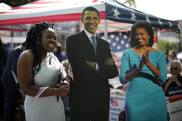 Immigrant Sheilla Nkwenji, 25, poses for a photo with cardboard cutouts of Barack and Michelle Obama outside a naturalization ceremony after becoming a new U.S. citizen in Los Angeles, California, U.S. March 20, 2018. REUTERS/Lucy Nicholson TPX IMAGES OF THE DAY