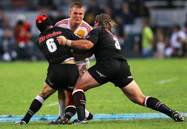 New Zealand Waikato Chiefs' Sam Cane (C) is tackled by Durban Sharks' players during a Super 15 rugby union match at the Mr Price Kings Park Rugby Stadium on April 21, 2012. AFP PHOTO (Photo credit should read -/AFP/Getty Images)