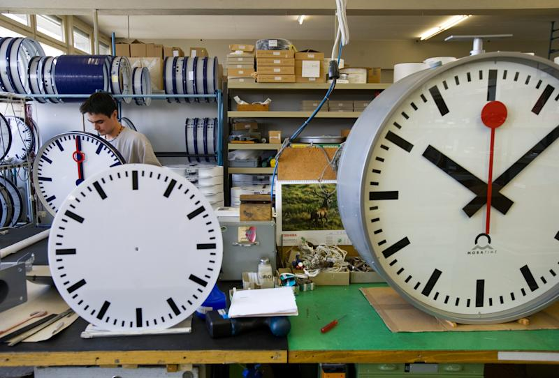 FILE - In this Sept. 21, 2005 file photo, an employee at Mobatime Swiss Inc. finishes a Swiss railway station clock at their factory in Sumiswald, Switzerland. Switzerland's national rail company is accusing Apple Inc. of stealing the iconic look of its station clocks for the iOS 6 operating system used on iPad mobile devices. (AP Photo/Keystone, Martin Ruetschi, File)
