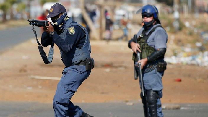 A member of the South African Police Services (SAPS) aim at looters following sporadic looting and vandalism outside the Lotsoho Mall in Katlehong township, East of Johannesburg, on July 12, 2021.