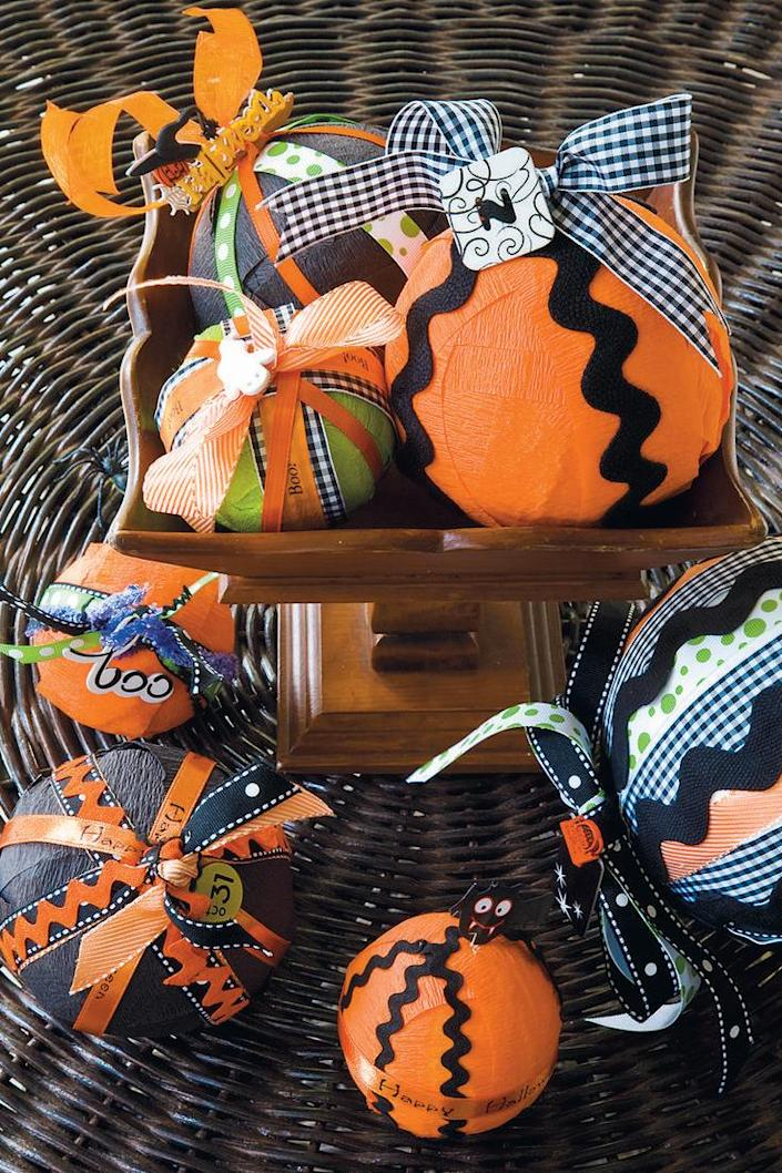 """<p>These charming Halloween-themed balls make the perfect centerpiece, and they're so easy to make.</p><p><strong><em><a href=""""https://www.womansday.com/home/crafts-projects/a28612676/charm-balls/"""" rel=""""nofollow noopener"""" target=""""_blank"""" data-ylk=""""slk:Get the Charm Balls tutorial"""" class=""""link rapid-noclick-resp"""">Get the Charm Balls tutorial</a>.</em></strong></p><p><a class=""""link rapid-noclick-resp"""" href=""""https://www.amazon.com/Craft-Foam-Balls-Sizes-Pack/dp/B0841SDBZ9?tag=syn-yahoo-20&ascsubtag=%5Bartid%7C10070.g.2488%5Bsrc%7Cyahoo-us"""" rel=""""nofollow noopener"""" target=""""_blank"""" data-ylk=""""slk:SHOP STYROFOAM BALLS"""">SHOP STYROFOAM BALLS</a></p>"""