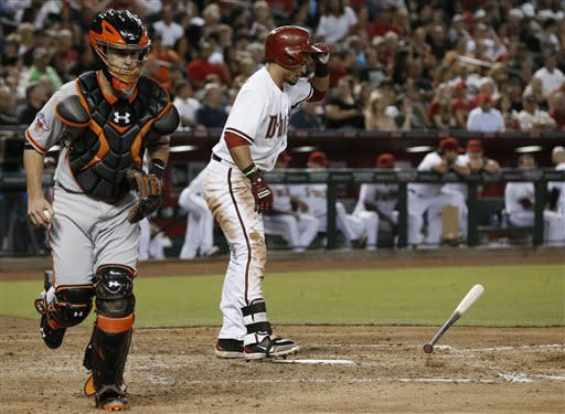 Arizona Diamondbacks' Gerardo Parra tosses his bat down after striking out as San Francisco Giants' Buster Posey runs back to the dugout at the end of the fifth inning in a baseball game Friday, June 7, 2013, in Phoenix. (AP Photo/Ross D. Franklin)