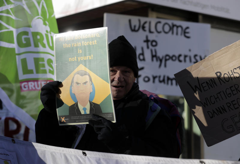 """A demonstrator holds up a poster with a picture of Brazilian President Jair Bolsonaro and the words """"Hi Jair Bolsonaro, the rain forest is not yours"""" during a protest outside the annual meeting of the World Economic Forum in Davos, Switzerland, Thursday, Jan. 24, 2019. (AP Photo/Markus Schreiber)"""