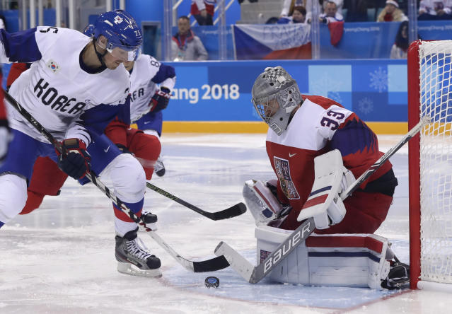 Brock Radunske (25), of South Korea, and goalie Pavel Francouz (31), of the Czech Republic, battle for the puck during the third period of the preliminary round at the 2018 Winter Olympics in Gangneung, South Korea, on Thursday. (AP)