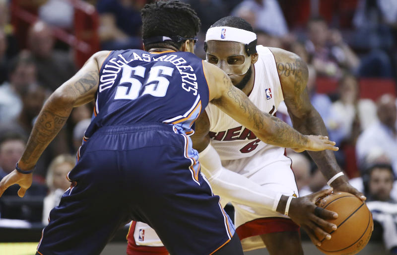 Charlotte Bobcats' Chris Douglas-Robert (55) tries to block Miami Heat's LeBron James (6) during the second half of an NBA basketball game in Miami, Monday, March 3, 2014. LeBron James scored a team record of 61 points. The Heat won 124-107. (AP Photo/J Pat Carter)