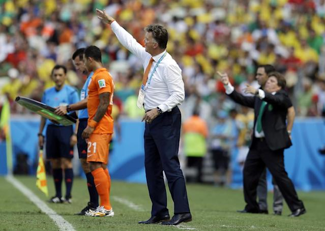 Netherlands' head coach Louis van Gaal, center, and Mexico's head coach Miguel Herrera, right, gesture during the World Cup round of 16 soccer match between the Netherlands and Mexico at the Arena Castelao in Fortaleza, Brazil, Sunday, June 29, 2014. (AP Photo/Natacha Pisarenko)