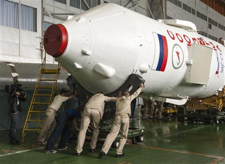 Specialists move the Soyuz TMA-16 spacecraft in the assembling hangar at the Baikonur cosmodrome, September 27, 2009. REUTERS/Shamil Zhumatov