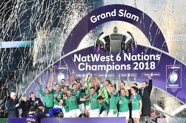 Ireland captain Rory Best holds the Six Nations trophy and fly-half Jonathan Sexton the Triple Crown as players celebrate (AFP Photo/Glyn KIRK )