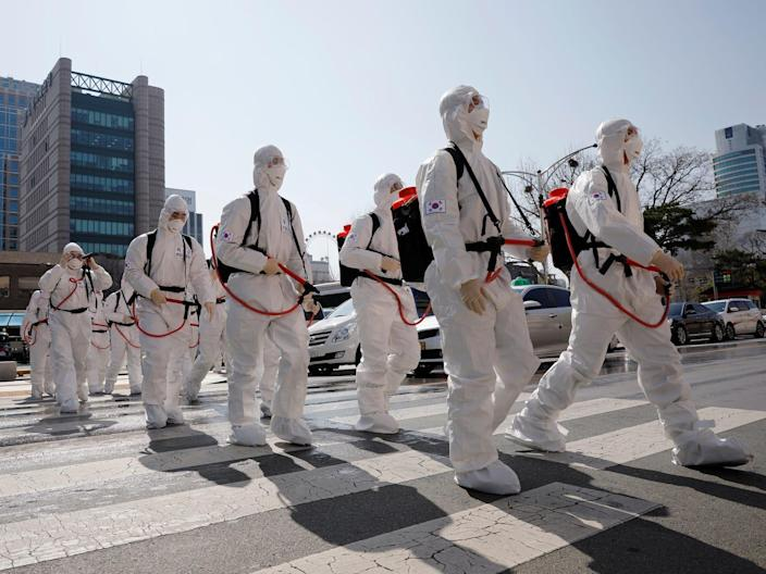 South Korean soldiers wearing protective gear walk on a street in front of Daegu's city hall after the rapid rise in confirmed cases of the coronavirus in the country, March 2, 2020.