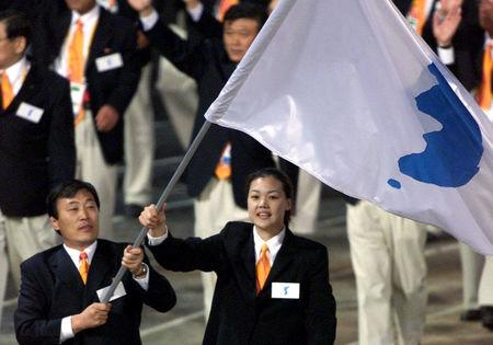 North Korea's Jang Choo Pak (L) and South Korea's Eun-Soon Chung carry a flag bearing the unification symbol of the Korean peninsula during the opening ceremony of the Sydney 2000 Olympic Games, in Sydney, Australia September 15, 2000. REUTERS/Andy Clark/Files