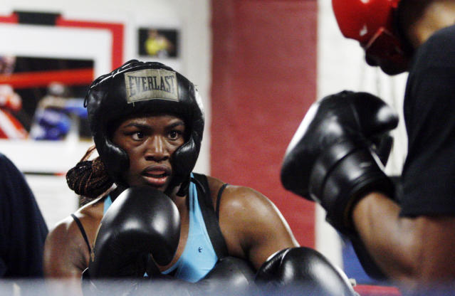 In this Sept. 18, 2012, photo, Olympic gold medal boxer Claressa Shields spars with training partner Ardreal Holmes at the Berston Field House in Flint, Mich. Aside from her Olympic title and a jab that could knock someone out cold, Shields isn't much different than other high school seniors. (AP Photo/Carlos Osorio)